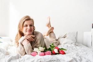Mujer feliz acostada en la cama con ramo de flores de tulipán foto