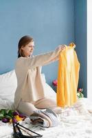 mujer organizando ropa sentada en la cama en casa foto