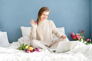 Mujer sentada en la cama en pijama charlando en el portátil foto