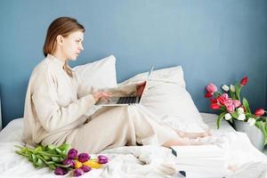 Mujer sentada en la cama vistiendo pijama bouquet charlando en el portátil foto