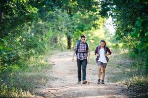 pareja joven caminando con mochilas en el bosque. caminatas de aventura. foto