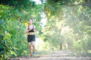 Young fitness woman running on a rural road. Sport woman running. photo