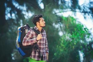 hombre caminante se relaja con una mochila grande durante la caminata en el bosque. foto