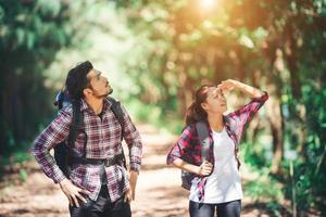 pareja joven deja de buscar algo durante el senderismo juntos. foto