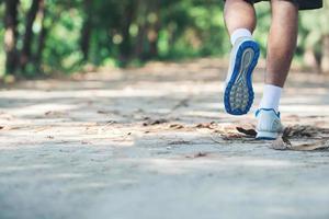 Cerca del pie del joven corredor corriendo a lo largo de la carretera en el parque. foto