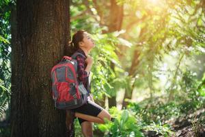 mujer caminante cansada se relaja con una mochila grande a pie en el bosque. foto