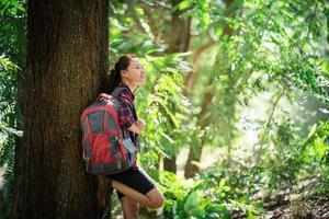 mujer caminante cansada se relaja durante la caminata en el bosque. foto