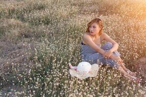 sexy hermosa mujer sentada en el campo de flores con tristeza y soledad foto