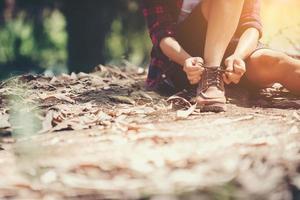 excursionista mujer se detiene para atar su zapato en una ruta de senderismo de verano en el bosque. foto