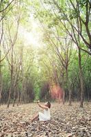 Hermosa joven reza por algo en el bosque verde foto