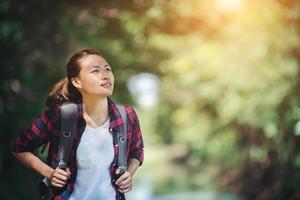 mujer de senderismo - excursionista caminando en el bosque verde. foto