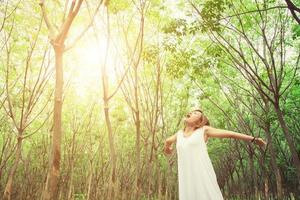 Young beautiful woman raised arms enjoying the fresh air in forest. photo