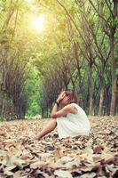 mujer triste se quita las manos de la cara tan tristemente sentada en una hoja seca. foto