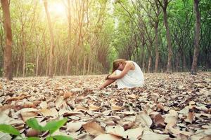 Joven mujer asiática tristemente sentada sobre hojas secas en el bosque solo foto