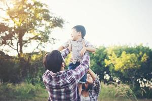 Happy young family spending time together outside in green nature park photo