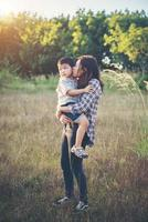 mamá abrazando a su pequeño niño caminando en el campo. al aire libre. foto