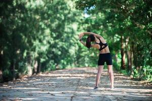 Young fitness woman stretching legs before run. photo