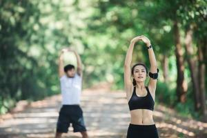 Man and woman stretching together at the park. photo