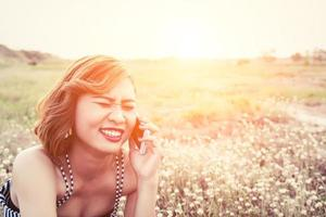 woman using a smartphone in flower field in summer laugh so happy photo