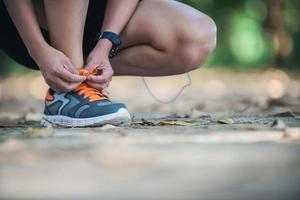 Young fitness woman sitting tie their shoes before she go jogging. photo