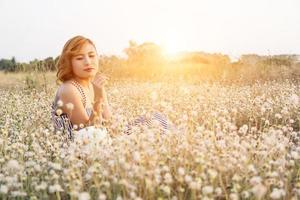 Sexy Beautiful woman sitting in flower field enjoy and smell at flower photo