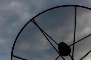 Primer plano de una antena parabólica en el cielo nublado por la noche foto