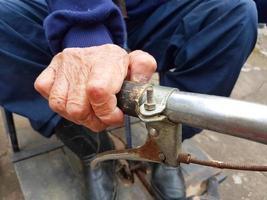 Cerca de la mano del anciano discapacitado sosteniendo la manija del triciclo foto