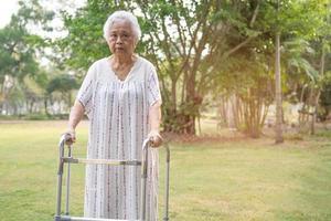 Mujer mayor asiática usa andador caminando en el parque foto