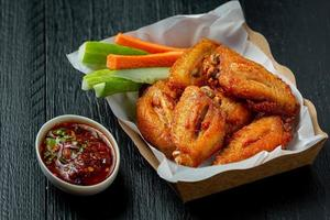 Chicken wings in paper box on a black photo