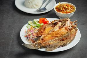 Fried snapper in a plate placed on a black background photo