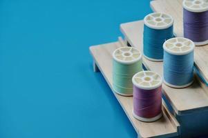 Grupo de hilo multicolor en el soporte de madera sobre el fondo azul. foto