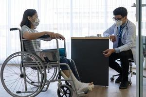 asian doctor examines  patient in wheelchair because of leg injury photo