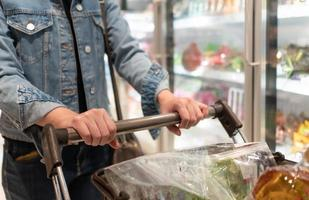 woman using shopping cart to buy groceries in supermarket photo