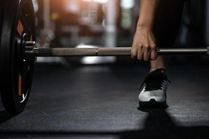 Closeup of young woman holding barbell photo