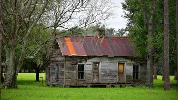 old abandoned farm house with rusty tin roof in North Florida photo