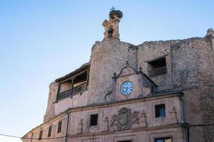 clock on the facade of a medieval building in Spain photo