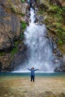 woman stand in front of beautiful waterfall. photo