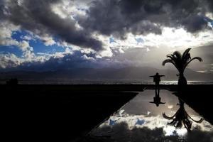 vista al mar y una silueta de hombre en el agua foto