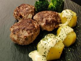 Fried meatballs with boiled broccoli and parsley potatoes photo