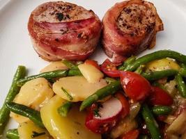 Pork tenderloin wrapped in bacon and salad photo