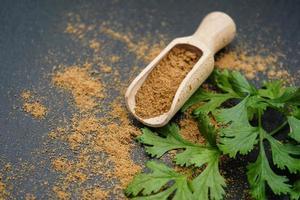 polvo de cilantro marrón y cuchara de madera foto