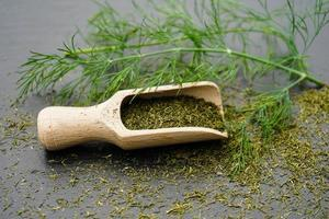 Dill Anethum graveolens and a wooden spoon photo