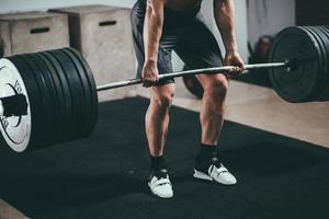 atleta vistiendo pantalones cortos negros levantando barra grande foto