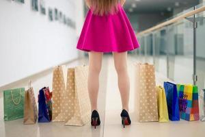 Cerrar mujer caminando con bolsas de la compra. foto