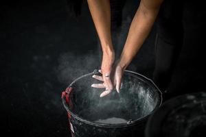 woman rubs his hands with chalk and talc so that fingers photo