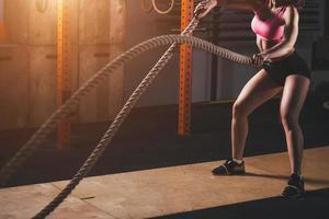 Mujer que trabaja en el gimnasio de entrenamiento haciendo ejercicio cross fit foto