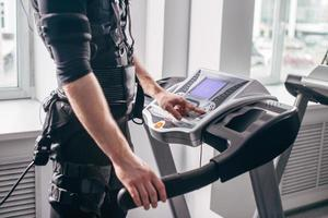 Man in black suit for ems training running on treadmill at gym photo
