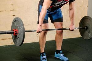 Levantador de pesas guapo preparándose para entrenar con barra foto