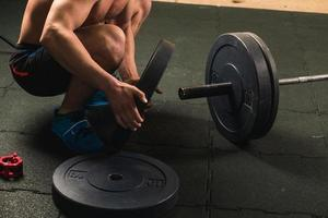 Handsome weightlifter preparing for training with barbell photo