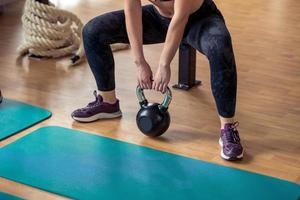 Group having functional fitness training with kettlebell in sport gym photo